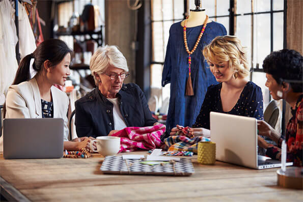 Four Fashion Designers In Meeting Discussing Textiles